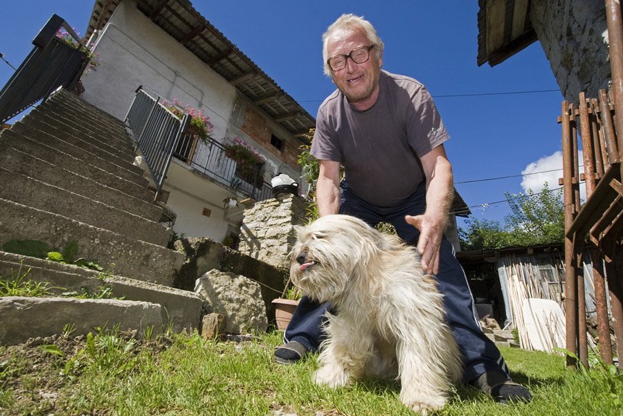 Rudi, one of the eight inhabitants of Robidišče, plays with his dog