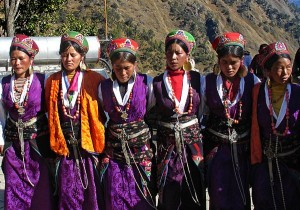 A group of young Nepalese women stand together wearing colourful traditional regional garb