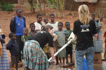 A visitor tries out the water pump at Millennium Villages Project in Mwandama