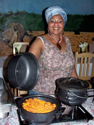 Liziwe Ngcolcoto prepares carrots in a potjie pot, a traditional South African style of cooking