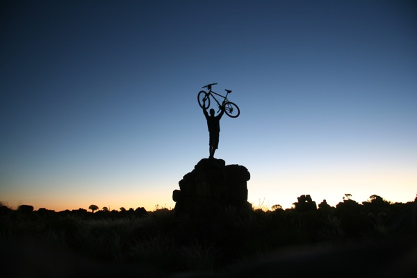 A Tour d'Afrique rider celebrates victory, holding his bike over his head at sunset (photo courtesy of Tour d'Afrique Ltd)