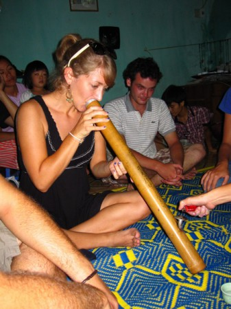 Tourists try smoking tobacco with a traditional Vietnamese water pipe