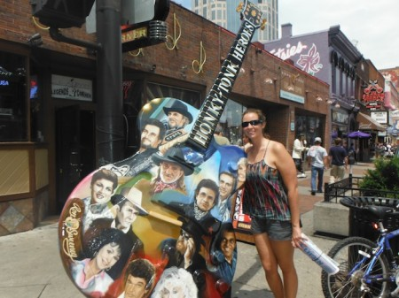 On Lower Broadway in Nashville, Tennessee, Nolan stands next to the 10-foot Honky-Tonk Heroes Guitar by artist Ron Sweeney