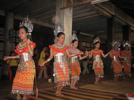 With soft and graceful movements, pretty Iban maidens perform the Ngajat dance in a longhouse