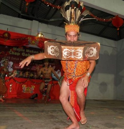 An Iban warrior performs the Ngajat Lesung dance, showcasing the strength of his teeth