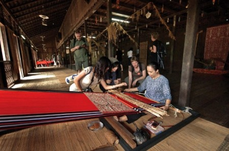 Travellers admire a woman making a Pua Kumbu, the unique and sacred craft of the Iban. Photo courtesy of Sarawak Tourism Board