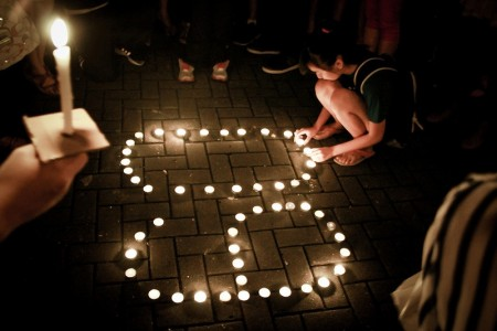 A kid lighting candles for Earth Hour