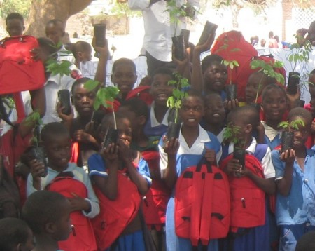 Children from the Makawa Primary School catchment in Malawi show off their saplings and Elephant Branded book bags