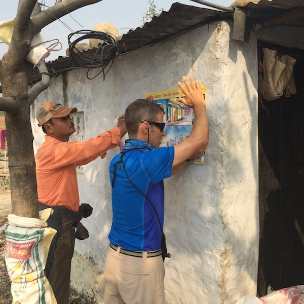 Tom Hodgman helps plaster posters in a village as part of an Maiti Nepal awareness event about human trafficking