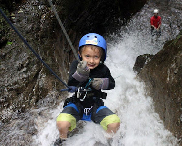 Ecotourism and family travel in Costa Rica: kid abseiling through a waterfall in Costa Rica