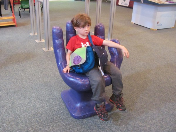 Kai sitting in a chair, shaped like a car