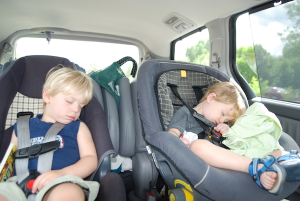 Kids asleep in a car during a family travel road trip