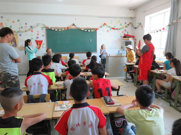 The authors' son Rohan performs magic tricks for the class at the Chinese migrant workers' school