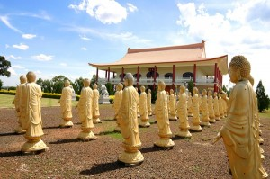 Statues confer positive energy to the grounds of the Buddhist Temple visible in the background