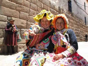 Two young girls in traditional Peruvian dress hold a little lamb in the exciting San Blas area of Cusco, Peru. San Blas, located near the main square, is where many artists congregate to display their works.