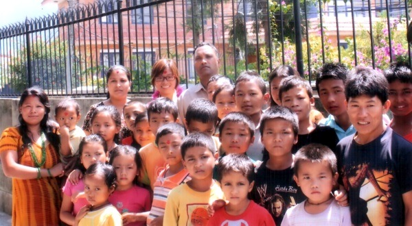 Mr Makhan Babu Pariyar (in the middle in the back), founder of the Orphan and Street Children Rehabilitation Centre of Kathmandu, Nepal, stands with the Centre's children and volunteers