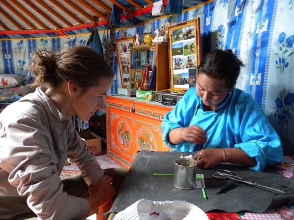 On a Ger to Ger cultural homestay program in Mongolia, visitors live and learn with rural communities and nomadic families. Here, inside a typical ger, a visitor learns how to sew with a nomadic woman in Terelj National Park. Other common activities include nomadic naadam (festivities), training Kazakh eagles, learning horse-head fiddle and more.