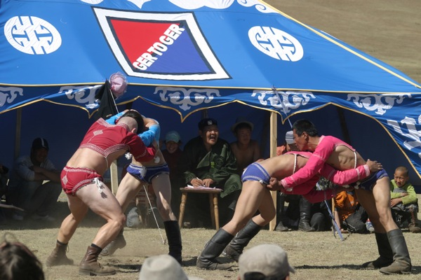 Visitors and locals watch Mongolian-style wrestling during a naadam (traditional Mongolian festival). The sport is somewhat similar to Greco-Roman wresting: the first man to touch the ground with anything but his feet loses, there are no weight classes and no time limits. The tradition two-piece costume consists of a tight-fitting vest (zodog) and shorts (shuudag).