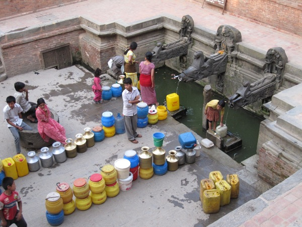 In Patan, Nepal, men and women line up to fill up their canteens at a well with government-provided water