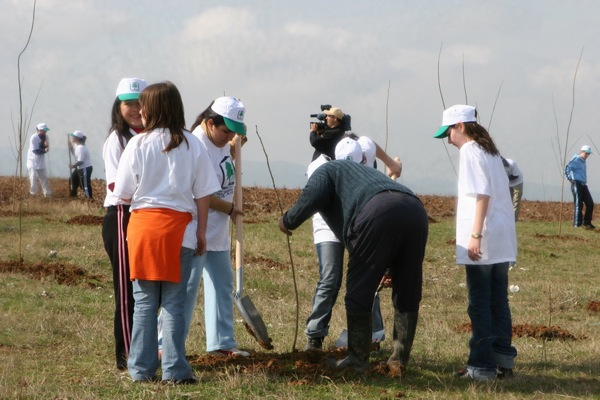 As part of the Green Belt initiative, school children get their hands dirty planting trees to help regenerate forests damaged by wildfires in Greece