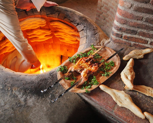 At the Bread House restaurant of Tbilisi, Georgia, travellers watch how traditional bread is baked in a special clay vessel called a 'tone,' which can also be used to roast pork and chicken