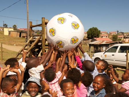 A group of preschool kids plays with a large branded ball