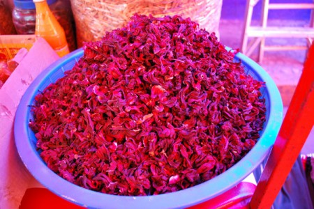 Red hibiscus iced tea in Belize uses hibiscus petals that are boiled in water and then strained and cooled