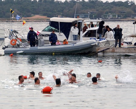 On the Theophany in Greece, swimmers attempt to retrieve a cross thrown into the cold waters of the local port