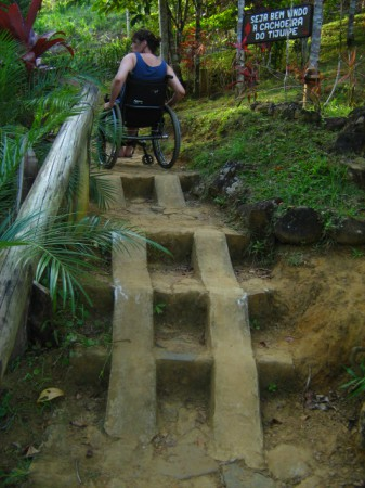 Person in wheelchair travels up steps in jungle using built-in ramps