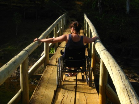 Person ina wheelchair crossing a rickety wooden bridge
