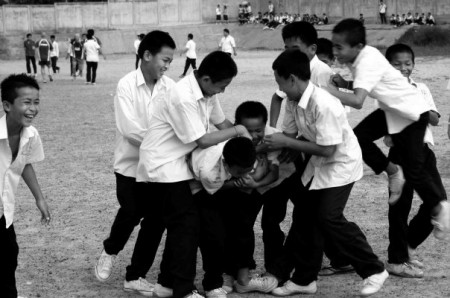 Grinning Lao boys play rugby