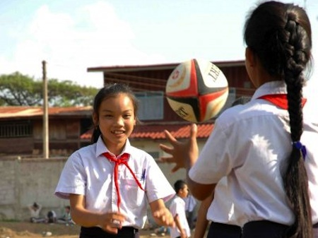 Lao girls playing with a rugby ball