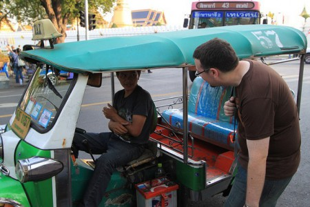 A foreigner negotiates with a tuk-tuk driver in Bangkok, Thailand