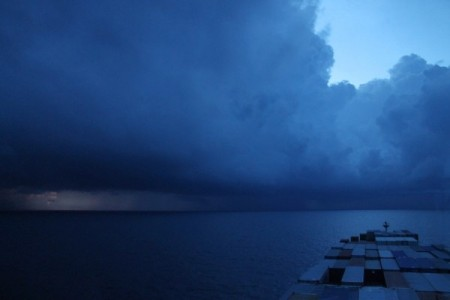 slow travel - cargo ships - storm clouds