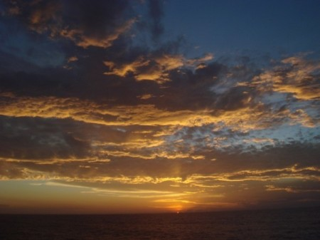 slow travel - cargo ships - sunset clouds