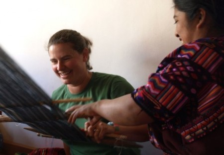 A visitor learns traditional back-strap weaving from an Oxlajuj B'atz' Maya teacher