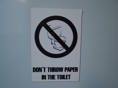 """don't throw paper in the toilet"" sign in Galapagos"