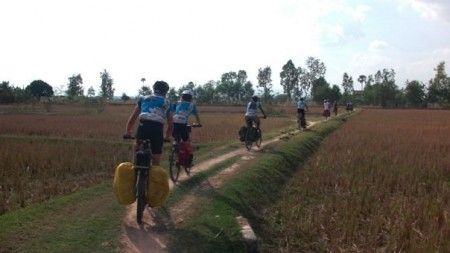 PEPY Riders venture along a path through rice paddies