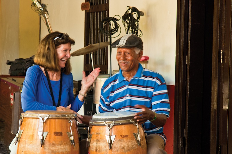 A visitor to the town of Trinidad, Cuba, meets with a local drummer