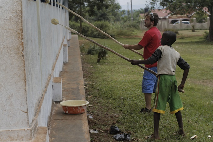Two volunteers paint at the Kivubuka Primary School in Jinja, Uganda