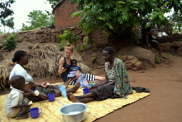 Alice Tilton sits with homestay hosts in Malawi