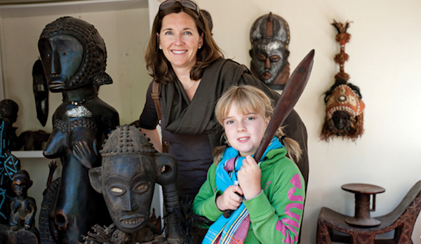Mother and daughter with African statues on a family safari in Africa