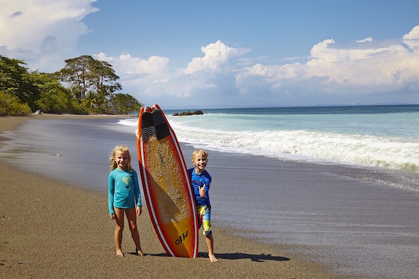 Ecotourism and family travel in Costa Rica: kids with a surf board on a beach in Costa Rica