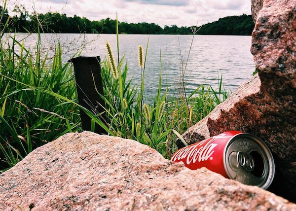 a Coke can by a river