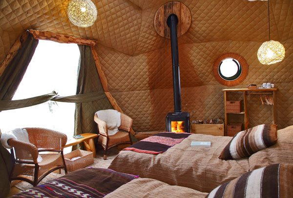 The camp at Torres del Paine, Chile, includes eco-domes with cozy beds and even a fireplaces